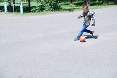 El muchacho que juega al fútbol, niño corre con la bola en el asfalto, jugador de equipo de fútbol, entrenando a forma de vida al Fotografía de archivo