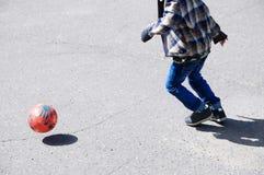 El muchacho que juega al fútbol, niño corre con la bola en el asfalto, jugador de equipo de fútbol, entrenando a forma de vida al Foto de archivo