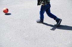 El muchacho que juega al fútbol, piernas del niño corre con la bola en el asfalto, jugador de equipo de fútbol, entrenando a form Imágenes de archivo libres de regalías