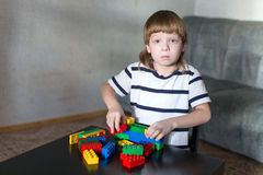 El muchacho que juega con las porciones de plástico colorido bloquea interior Fotografía de archivo