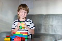 El muchacho que juega con las porciones de plástico colorido bloquea interior Fotos de archivo