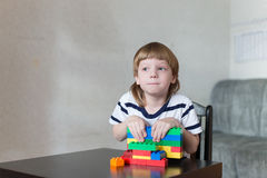 El muchacho que juega con las porciones de plástico colorido bloquea interior Imagen de archivo libre de regalías