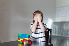 El muchacho que juega con las porciones de plástico colorido bloquea interior Fotos de archivo libres de regalías