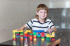 El muchacho que juega con las porciones de plástico colorido bloquea interior Imagen de archivo