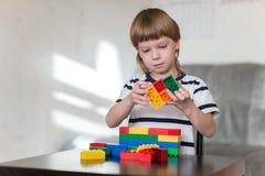 El muchacho que juega con las porciones de plástico colorido bloquea interior Imágenes de archivo libres de regalías