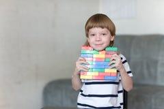 El muchacho que juega con las porciones de plástico colorido bloquea interior Foto de archivo libre de regalías