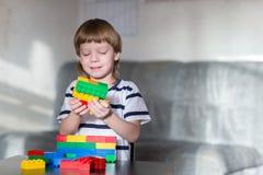 El muchacho que juega con las porciones de plástico colorido bloquea interior Foto de archivo
