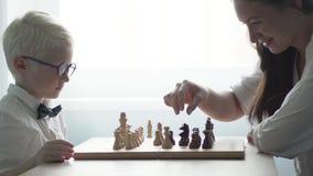 El muchacho que juega con su madre en ajedrez almacen de metraje de vídeo