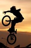El muchacho que juega trucos de la bicicleta Fotografía de archivo libre de regalías