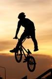 El muchacho que juega trucos de la bicicleta Fotos de archivo libres de regalías