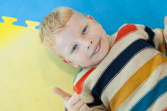 El muchacho que miente en demostraciones de piso coloridas manosea con los dedos para arriba Imagen de archivo libre de regalías