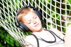 El muchacho que miente en una hamaca y escucha la música en los auriculares Verano Imagen de archivo
