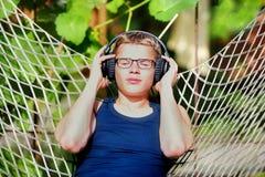 El muchacho que miente en una hamaca y escucha la música en los auriculares Verano Imágenes de archivo libres de regalías