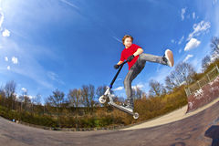 El muchacho que monta una vespa está saltando Fotografía de archivo libre de regalías