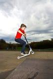 El muchacho que monta una vespa está saltando en Fotos de archivo