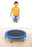 El muchacho que salta arriba en el trampolín Imagen de archivo libre de regalías