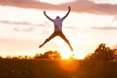 El muchacho que salta arriba para la felicidad contra puesta del sol Fotografía de archivo