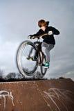 El muchacho que salta con su bici de la suciedad Foto de archivo libre de regalías