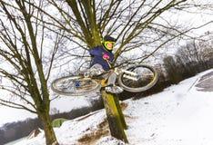 El muchacho que salta con su bici sobre una rampa en nieve imagen de archivo libre de regalías