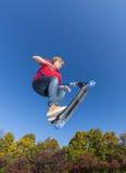 El muchacho que salta con su vespa en el parque del patín Fotografía de archivo