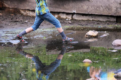 el muchacho que salta de roca a lo largo de la parte inferior de una fuente vieja quebrada Imagen de archivo