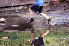 el muchacho que salta de roca a lo largo de la parte inferior de una fuente vieja quebrada Fotografía de archivo