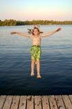 El muchacho que salta en el lago Fotografía de archivo libre de regalías