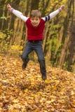 El muchacho que salta en el outumn más forrest Imagen de archivo libre de regalías