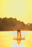 El muchacho que salta en el río Foto de archivo