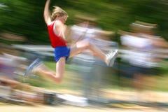 El muchacho que salta en la falta de definición de /motion de la reunión de pista Foto de archivo libre de regalías