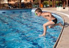 El muchacho que salta en la piscina Imagen de archivo