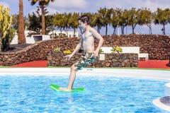 El muchacho que salta en la piscina azul Foto de archivo