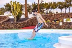 El muchacho que salta en la piscina azul Fotografía de archivo