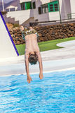 El muchacho que salta en la piscina azul Imagen de archivo libre de regalías