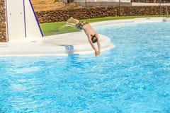 El muchacho que salta en la piscina azul Imagenes de archivo