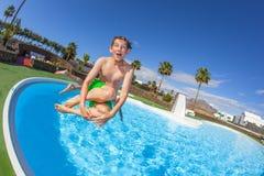 El muchacho que salta en la piscina azul Imágenes de archivo libres de regalías