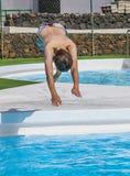 El muchacho que salta en la piscina azul imagen de archivo
