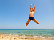 El muchacho que salta en la playa Fotos de archivo