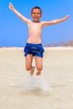 El muchacho que salta en la playa Imagen de archivo
