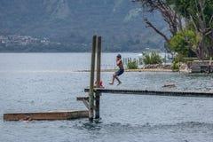El muchacho que salta en las aguas del lago Atitlan del embarcadero de San Marcos la Laguna - San Marcos La Laguna, lago Atitlan, Imagenes de archivo