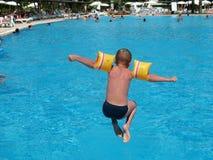 El muchacho que salta en piscina Imagenes de archivo