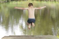 El muchacho que salta en un lago Fotos de archivo