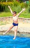 El muchacho que salta en una piscina Imagenes de archivo