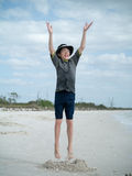 El muchacho que salta para la alegría en la playa Imágenes de archivo libres de regalías