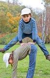 El muchacho que salta sobre la muchacha en parque del otoño en una hierba Imágenes de archivo libres de regalías