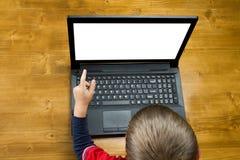El muchacho que señala al ordenador portátil de la pantalla Foto de archivo libre de regalías