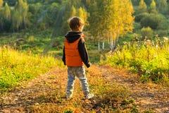 El muchacho que se coloca en el borde del bosque Imagenes de archivo