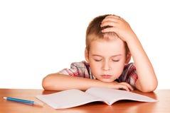 El muchacho que se sentaba en la tabla se cayó dormido en el libro de ejercicio aislado Imagen de archivo libre de regalías