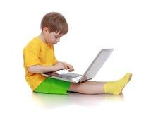 El muchacho que se sienta en el ordenador Fotos de archivo libres de regalías