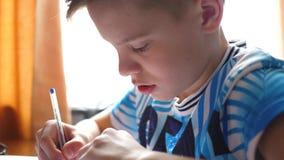 El muchacho que se sienta en el escritorio de la escuela y hace el trabajo Educaci?n escolar El ` s del sol irradia a trav?s del  almacen de metraje de vídeo